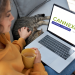 woman sitting on couch using laptop with cat beside her