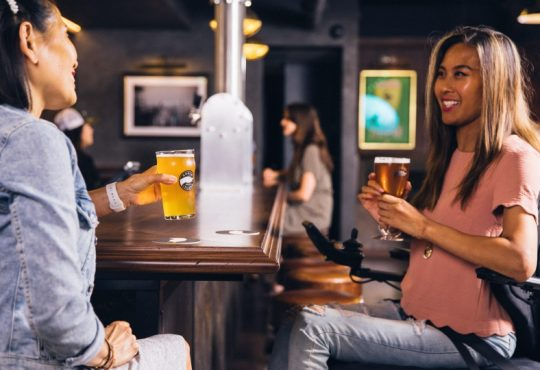 woman in wheelchair drinking beer in bar and talking to other woman