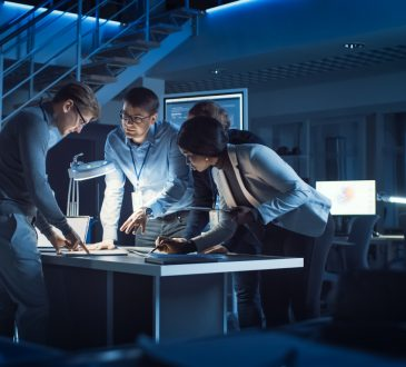 group of engineers working around table in office at night