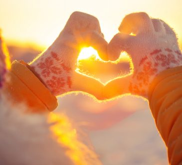 hands in winter gloves making heart shape with sunset behind