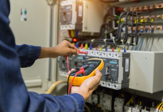 electrician measuring voltage and current of power electric line