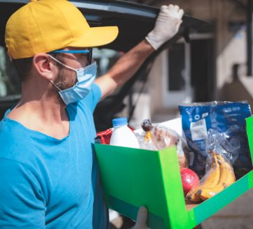 Delivery guy with protective mask and gloves delivering groceries during lockdown and pandemic.