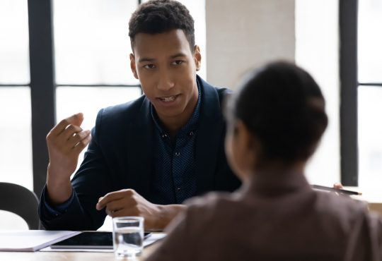 young man talking to manager in office