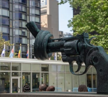 statue of gun tied into knot in front of United Nations building in New York