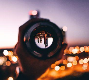 looking through telescope at city at night