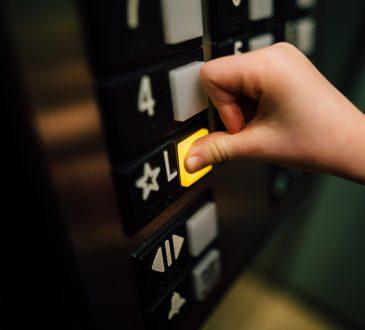 person pressing elevator button