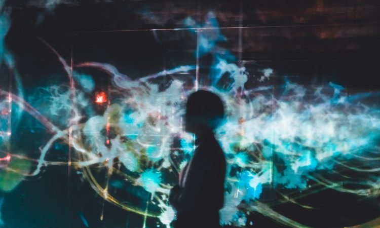 person silhouetted on background with colourful light patterns