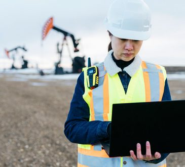woman standing in field wearing hard hat and holding laptop in hand