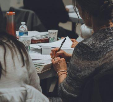 women sitting at table writing
