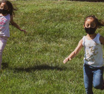 two little girls running on grass
