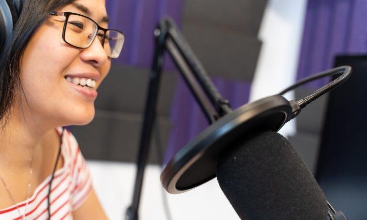 woman recording podcast wearing headphones