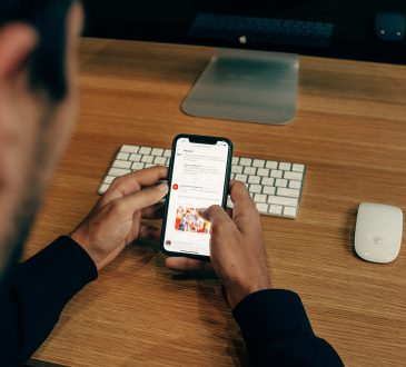 man scrolling through social media on cellphone