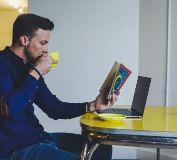 Man drinking coffee and reading book at kitchen table