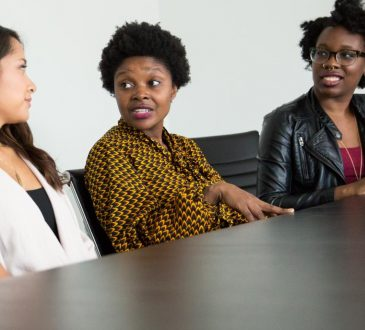 three black women sitting at boardroom table
