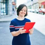 woman with down syndrome using tablet outside