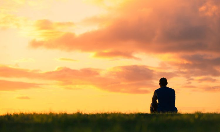 man sitting in field watching sunset