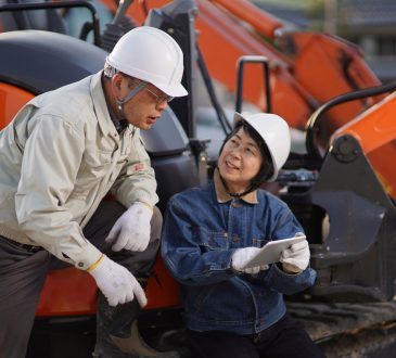 Two workers talking at a construction site