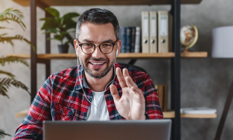 Middle aged man having video call from workplace at home