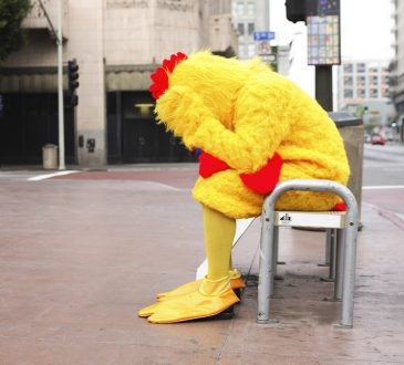 person wearing chicken mascot costume with head in hands on bench