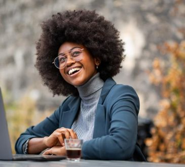 woman sitting at laptop outside looking happy