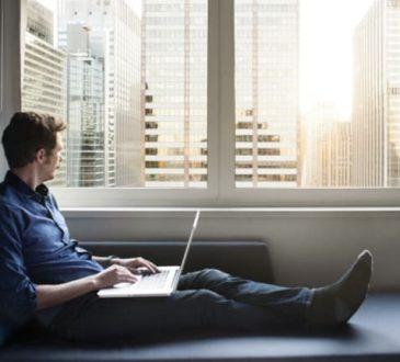 man working on laptop looking out window