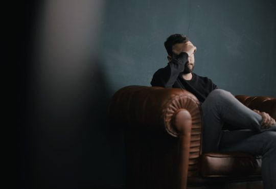 man sitting on couch looking depressed