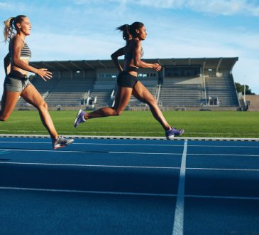 two women sprinting toward finish line on outdoor track