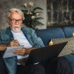 older man writing notes in notebook watching webinar
