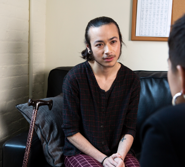 A genderqueer person sitting on a couch talking to a counsellor
