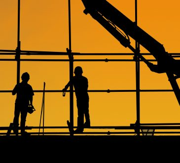 workers silhouetted at construction site