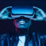 man smiling and wearing virtual reality headseat