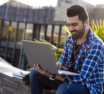 Male student Outdoors on laptop