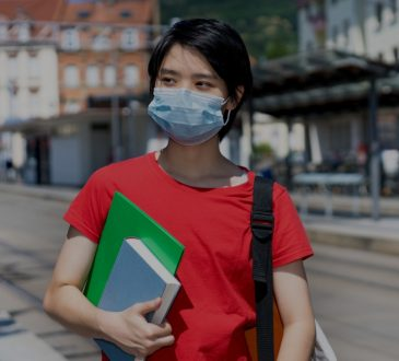 student holding books and walking down city street wearing mask
