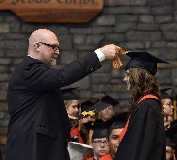 man putting graduation cap on student