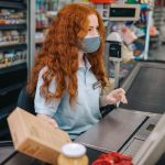 Female grocery store worker working at checkout counter.