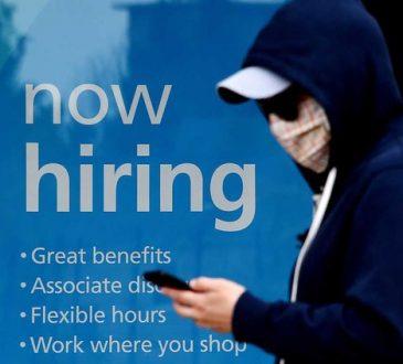 masked person walking past hiring sign
