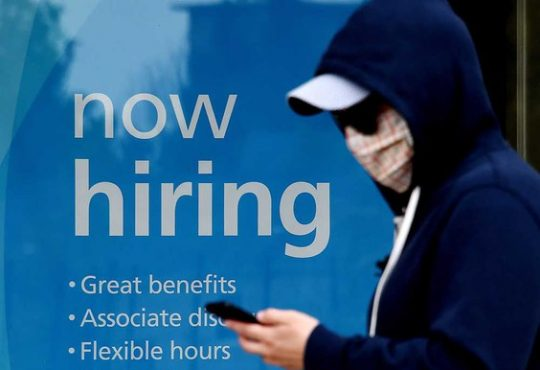 masked person walking past hiring sign