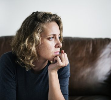 woman sitting on couch looking worried