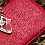 red passport cover with canadian flag keychain on top