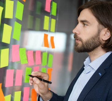 man in office writing on sticky notes on glass wall