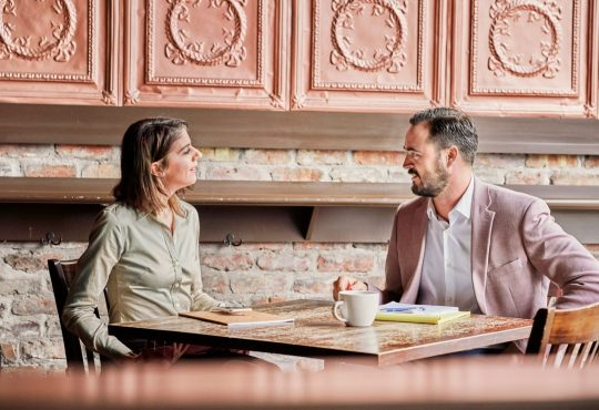 man and women in interview in restaurant or cafe