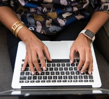 closeup of woman's hands typing on laptop