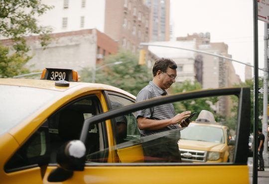 taxi driver leaning on car