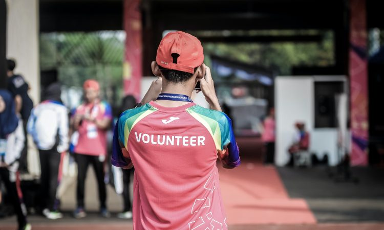 "man wearing shirt with ""volunteer"" on the back taking photo at outdoor event"