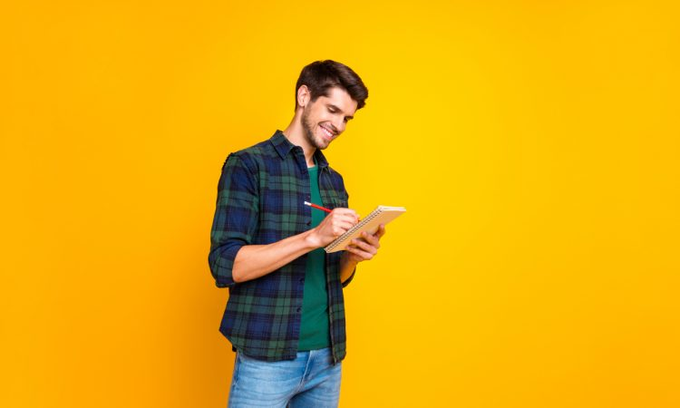 man standing and writing in notebook against bright yellow background