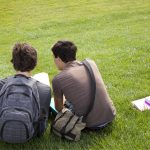 two male students with homework sitting on grass