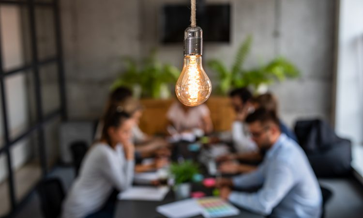 light bulb glowing over office meeting at table