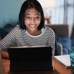 teen girl smiling while looking at tablet