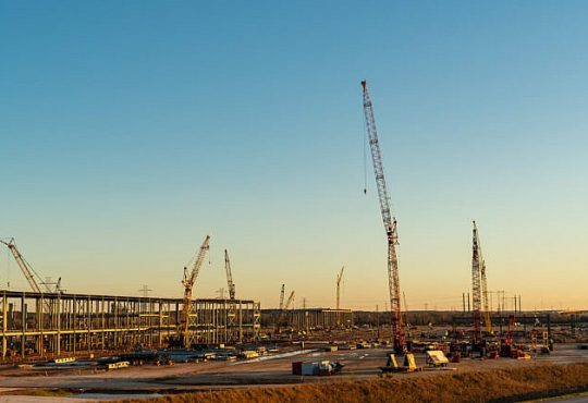 Cranes and large steel columns at Tesla GigaFactory under construction in Austin Texas.