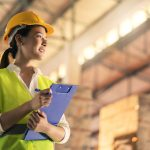 female engineer inspector wearing hard hat and holding clipboard